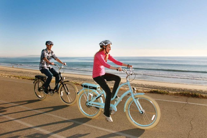 Two riders, each on a Townie, riding on paved bike path